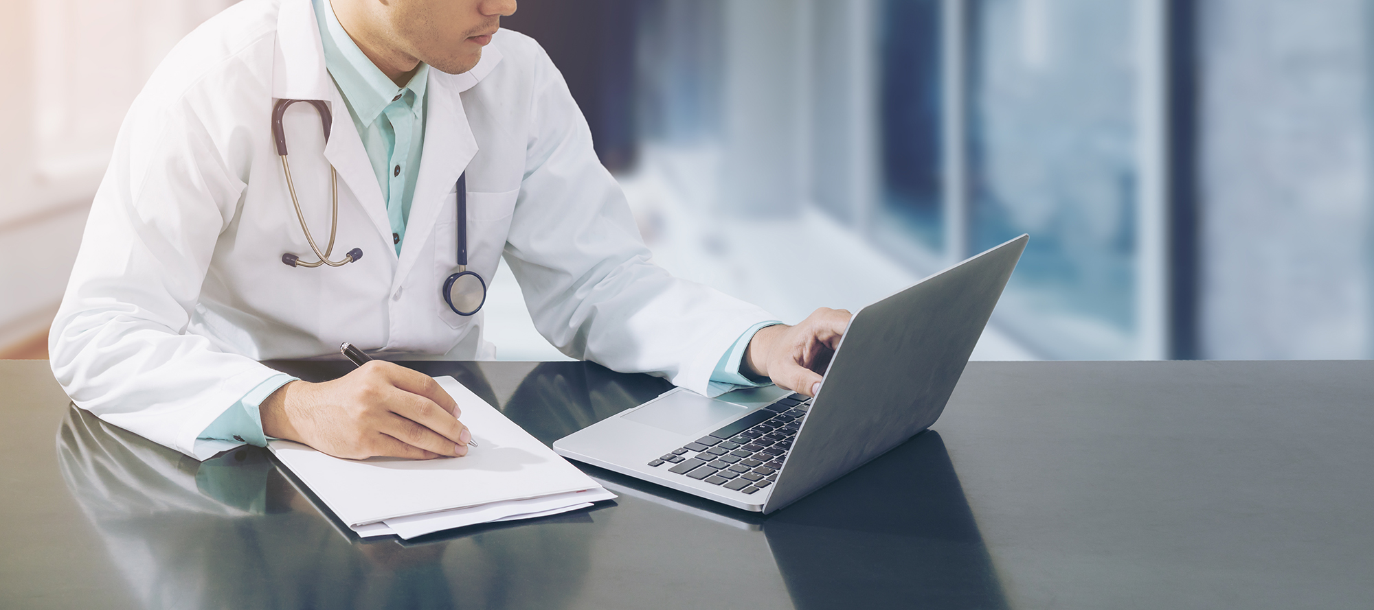 Doctor using a computer while taking notes.